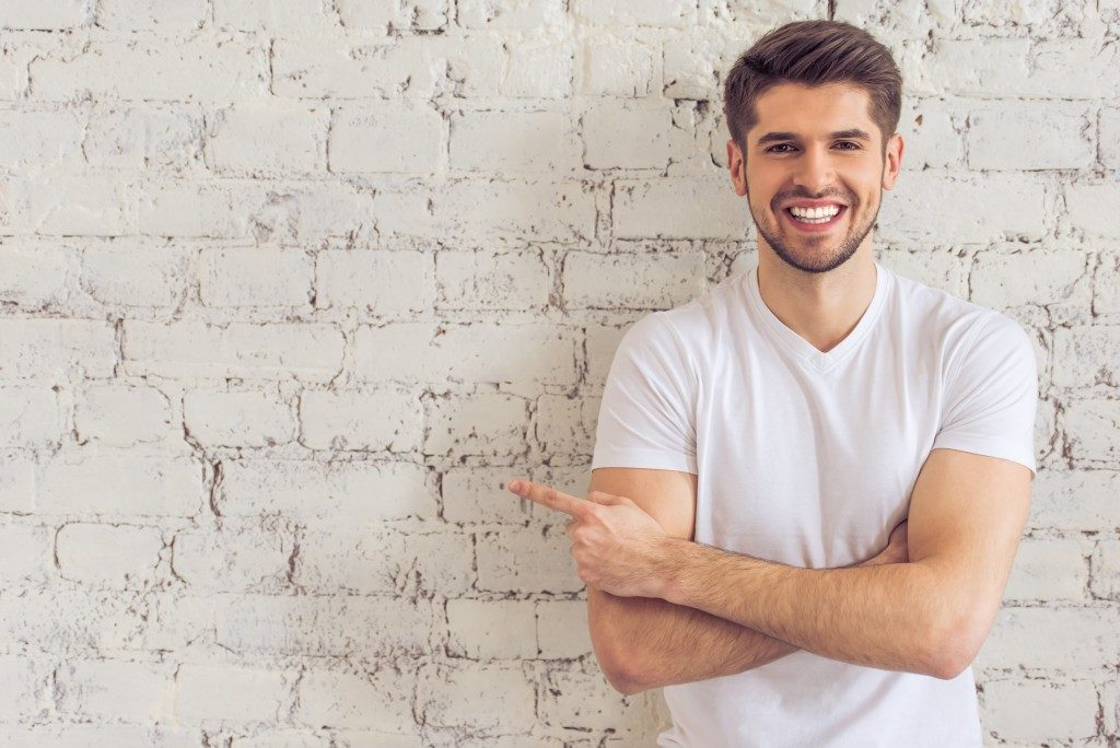 Man pointing at a white wall