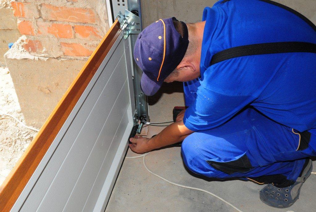 man checking garade door roller