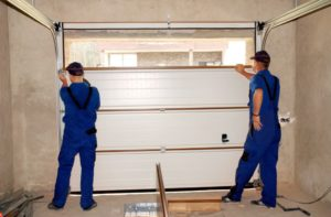 Contractors fixing a garage door