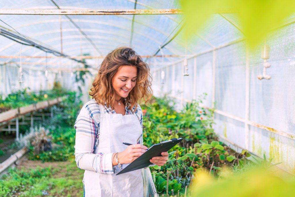 Woman holding clipboard in greenhouse