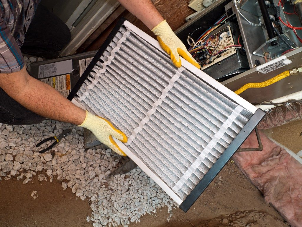 rconditioning repair man performing filter maintenance