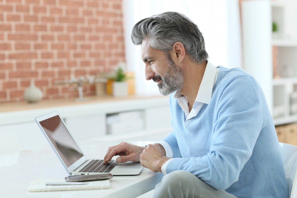 Trendy mature man working from home with laptop
