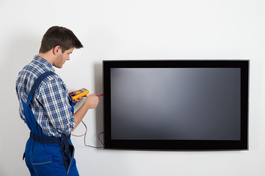 Electrician fixing a television