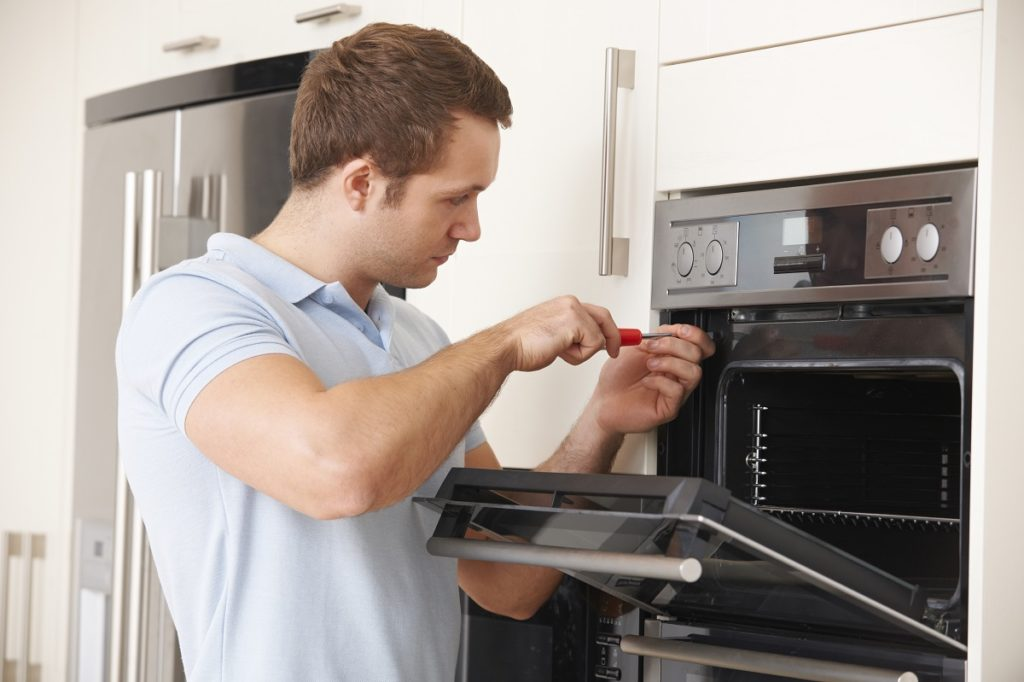Man repairing an oven using a screw