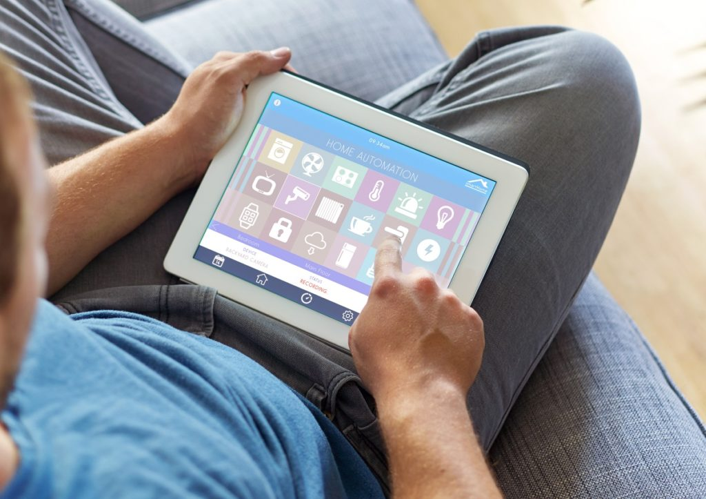Man using a tablet to control home appliances