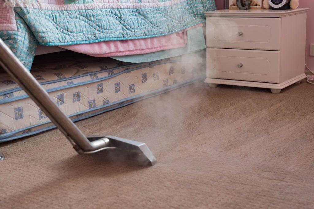Steam vacuuming the bedroom carpet