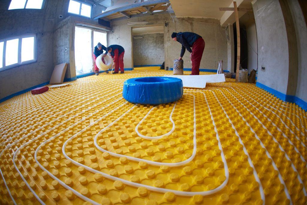 Workers intalling underfloor heater