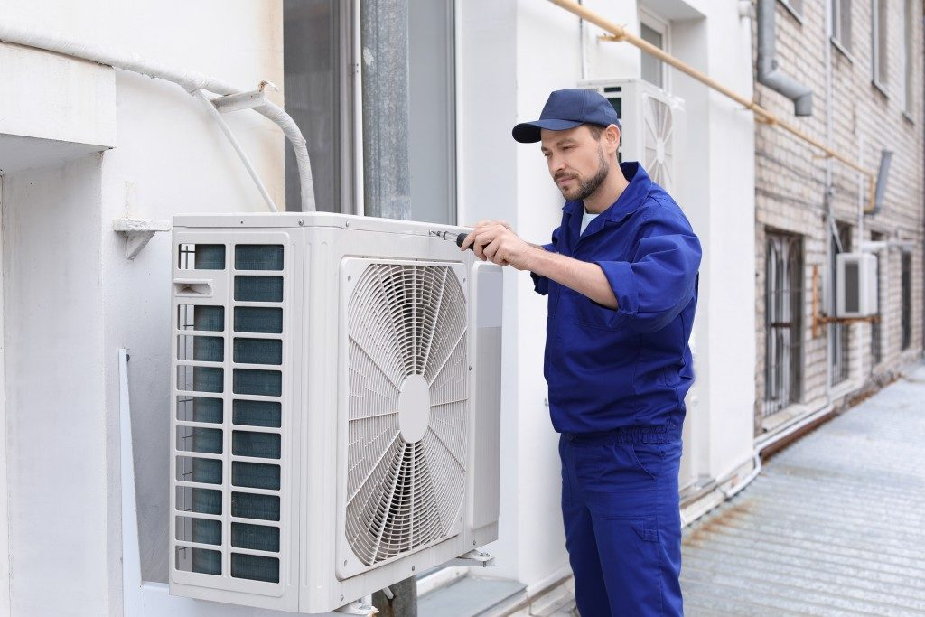 technician repairing fan of conditioning unit