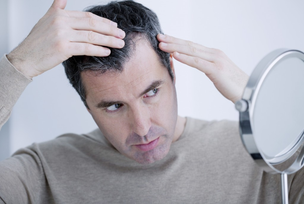 Man looking at his hair with a mirror