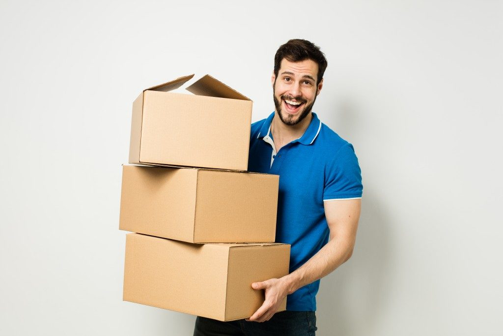 Man holding boxes for storage