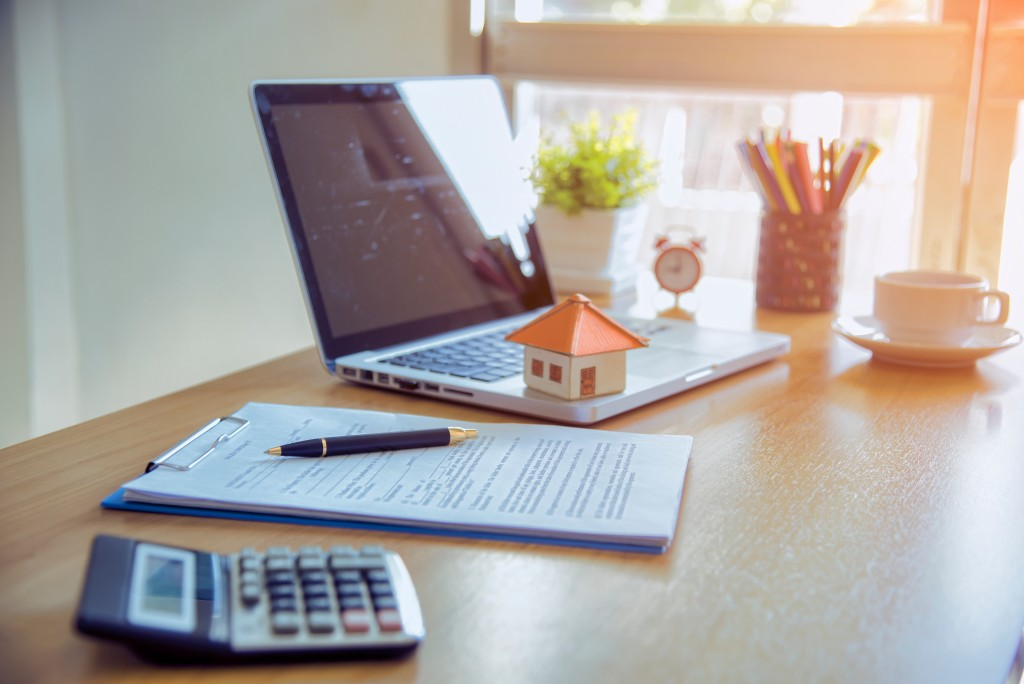 Calculator, document and laptop with small model house