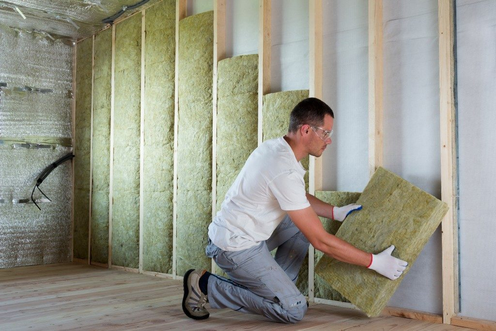 man putting insulation for drywall