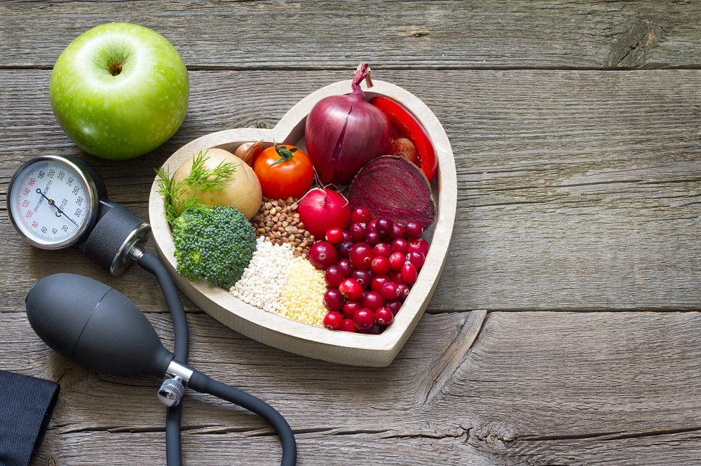 blood pressure pump next to heart shaped bowl with food