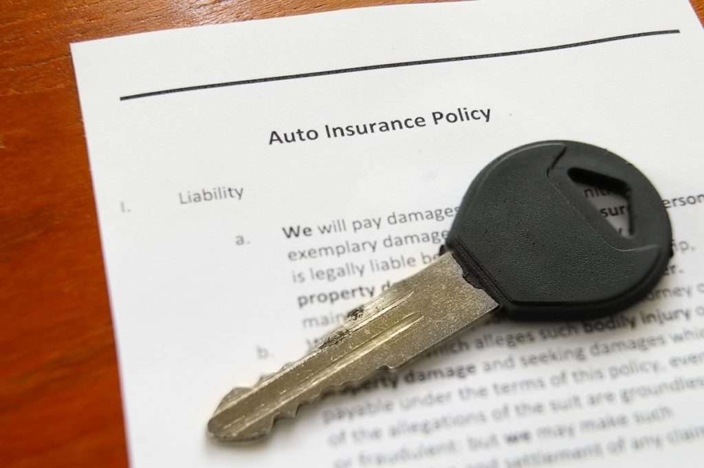 Auto insurance policy form with car key on top