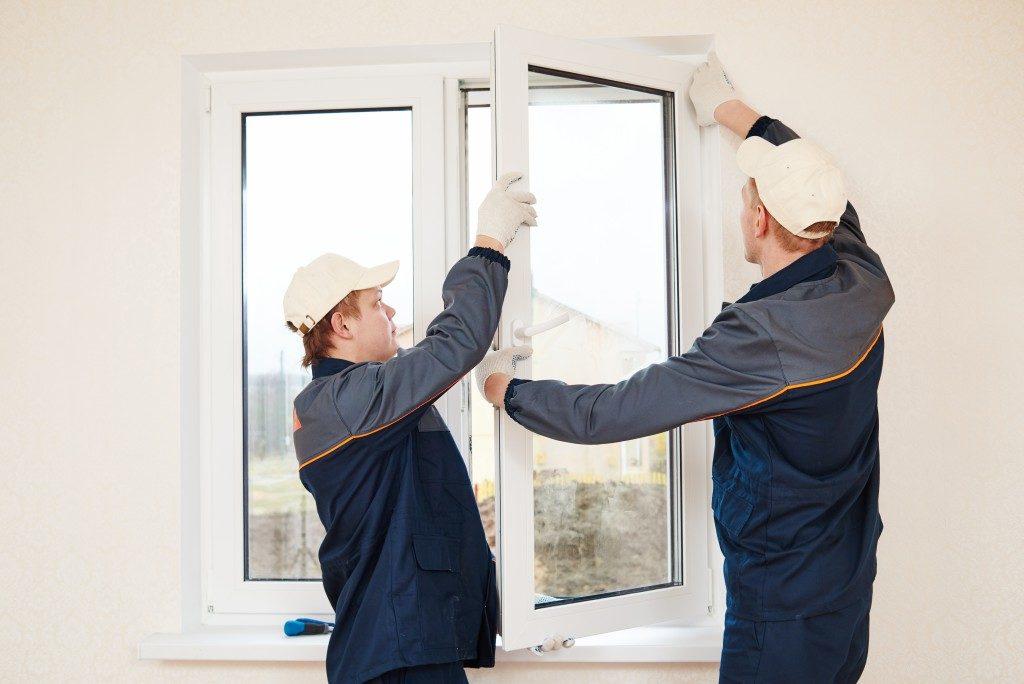 two men repairing window frames