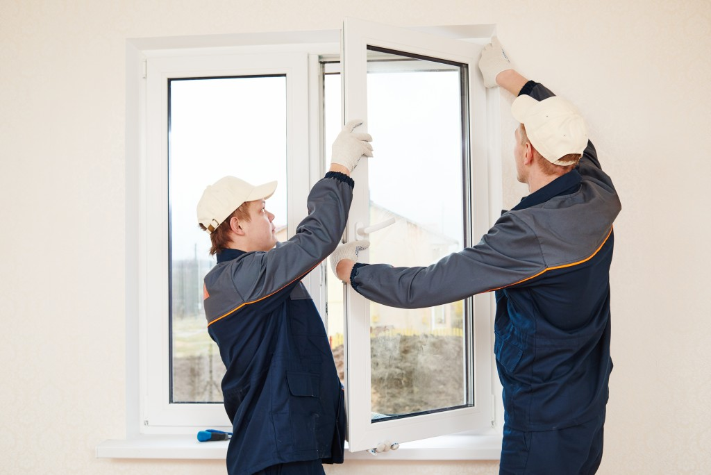 two men repairing window frames
