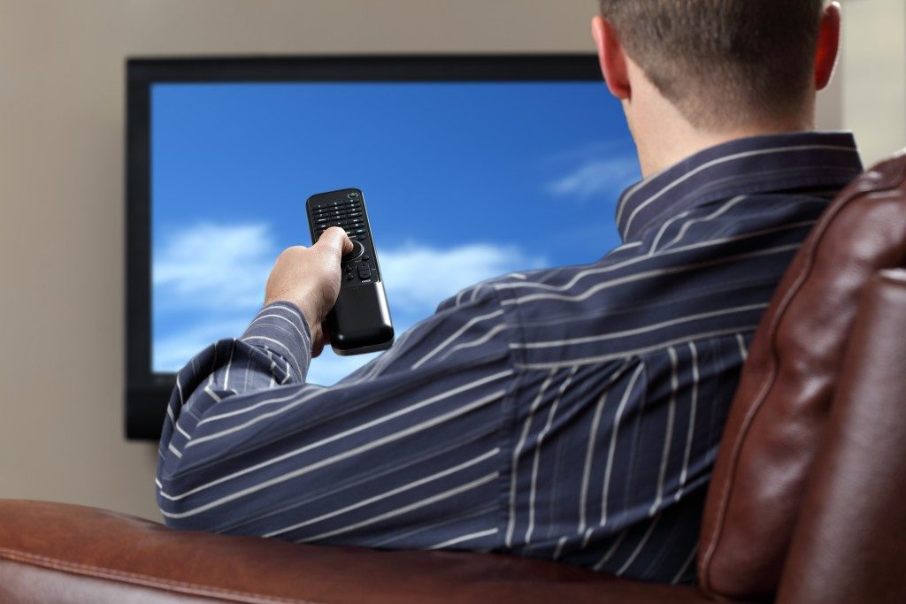 Man sitting on a sofa watching TV and holding a remote