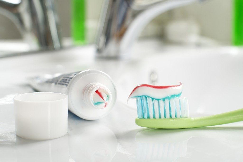 Toothpaste on toothbrush in the bathroom