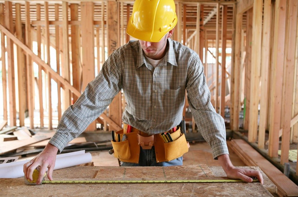 Man measuring plank in construction site