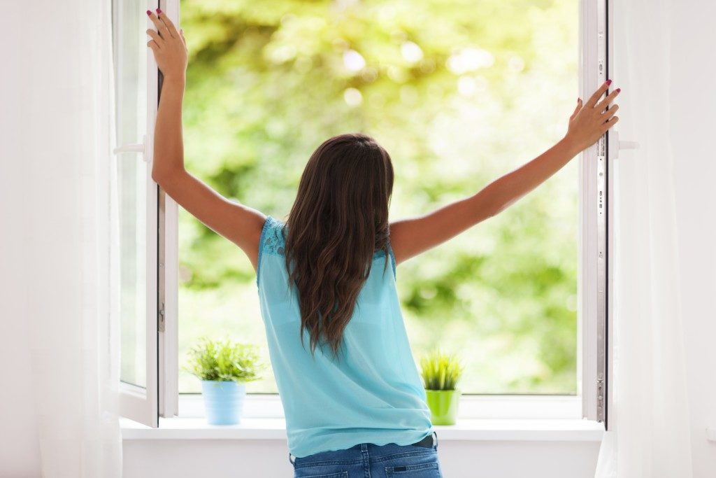 Woman opening her windows for air to come in
