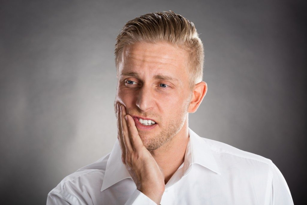 Man Suffering From Toothache Against Grey Background