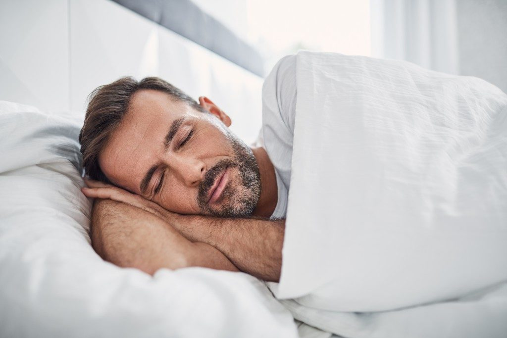 man sleeping in a comfortable bedding