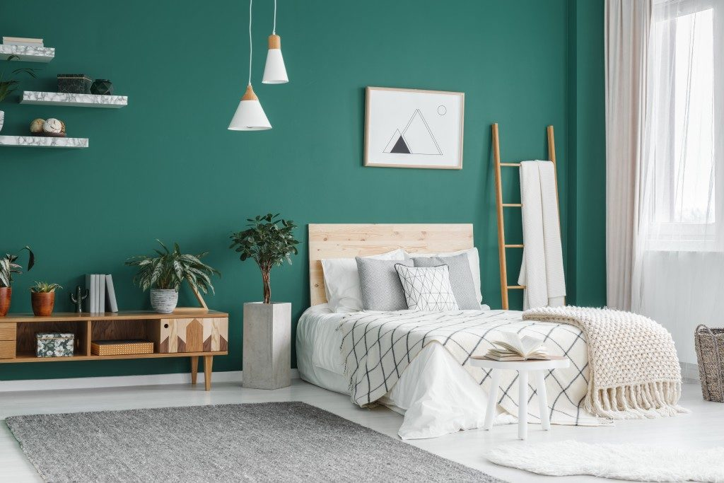 clean and airy bedroom with boho theme and teal wall