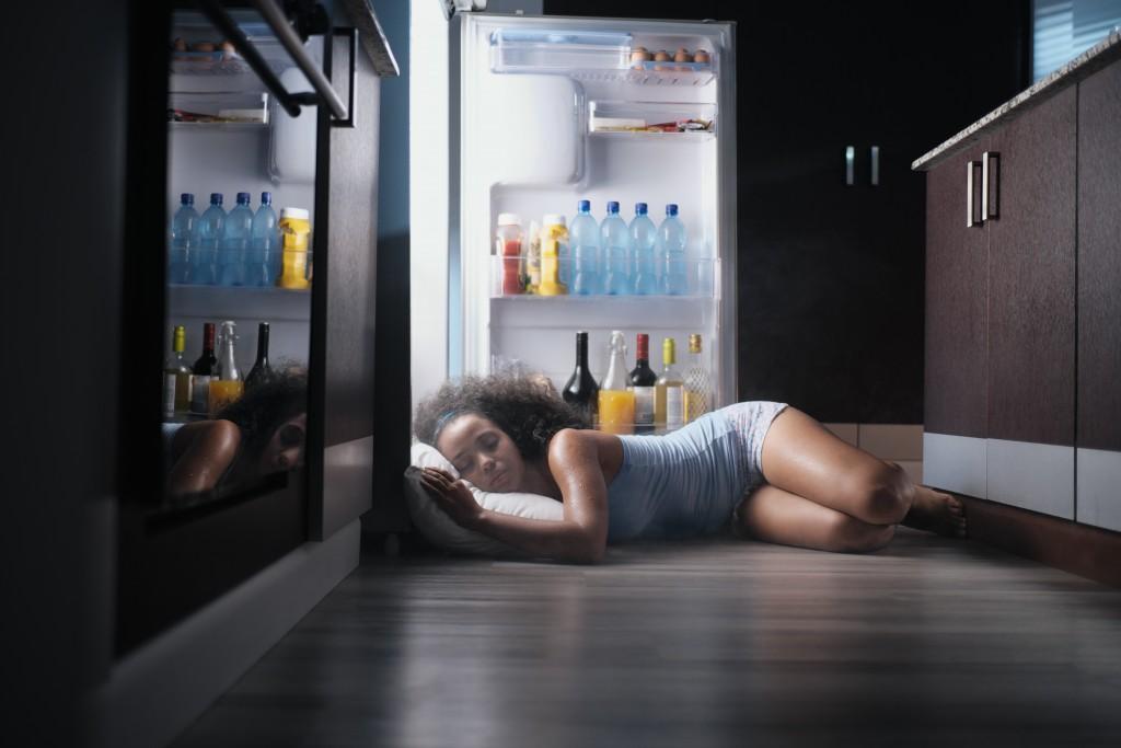 Woman sleeping infront an opened fridge