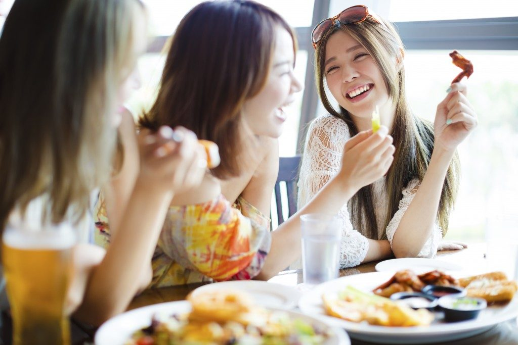girl talking to her friends while holding a chicken wing
