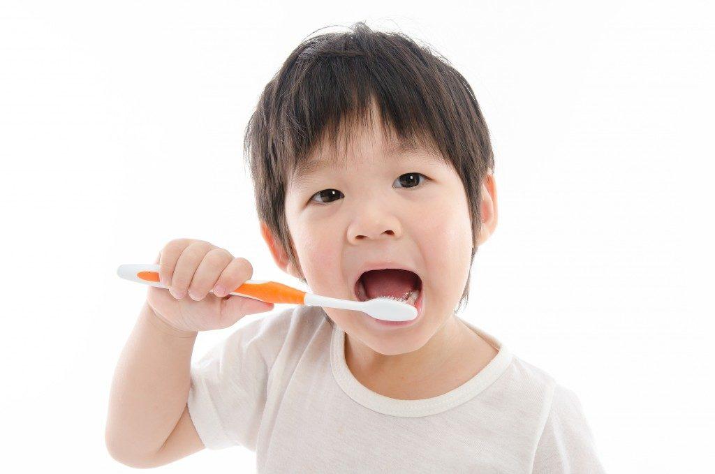 Asian boy brushing his teeth