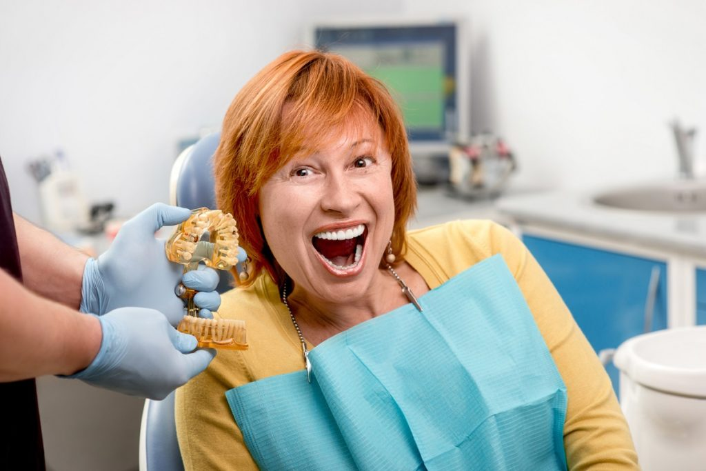 old woman smiling next to a mold of teeth