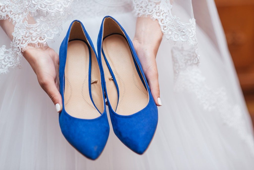 Bride holding wedding shoes blue
