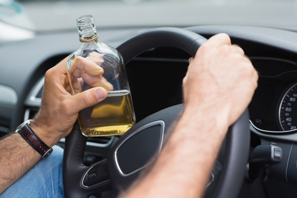 man drinking alcohol while driving