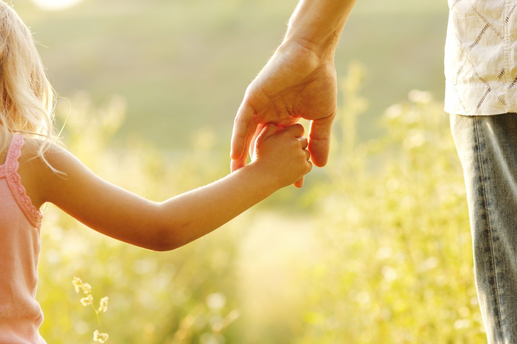 Young girl holding dad's hand