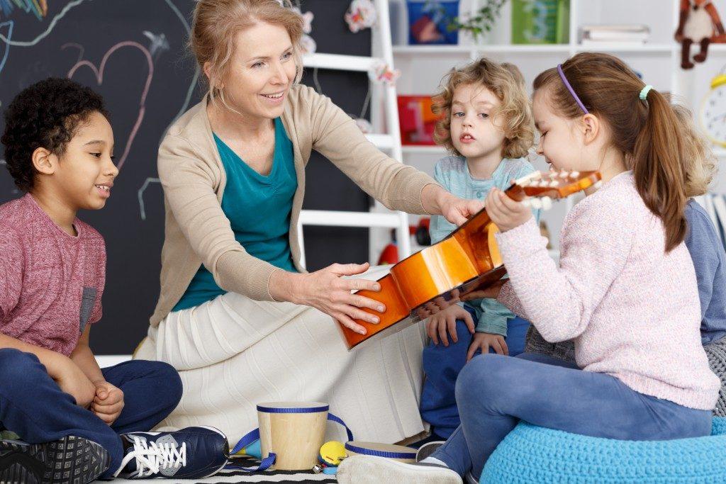 teacher handing guitar to her student