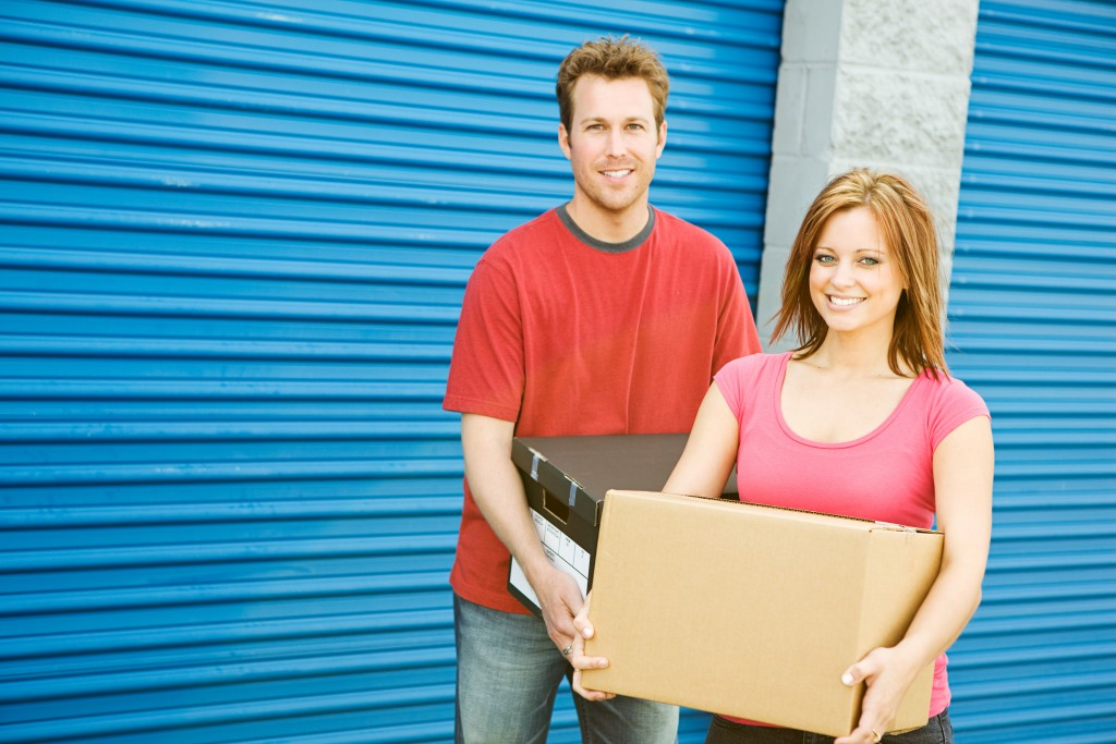 couple carrying boxes for storage