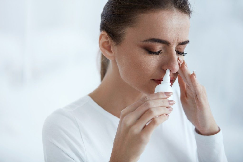 woman flushing out her sinuses