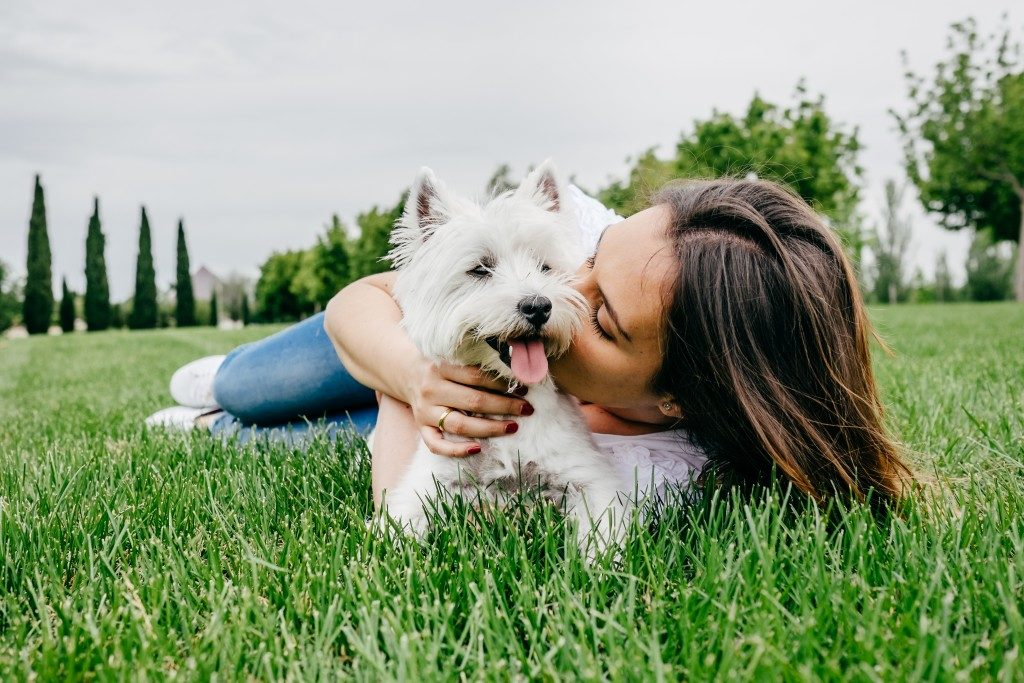 Woman kissing her pet dog