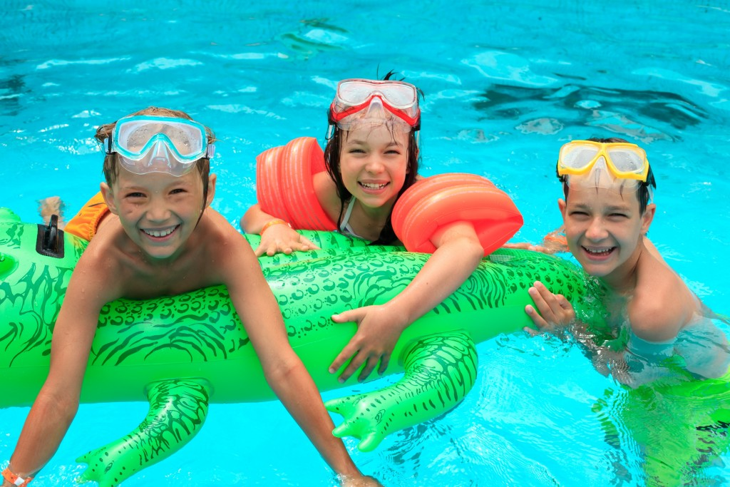 Children swimming in the pool with floaters