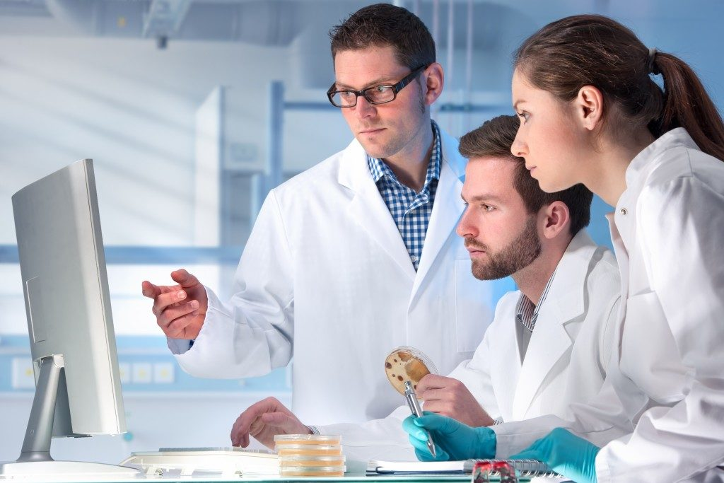Three scientists looking at the monitor