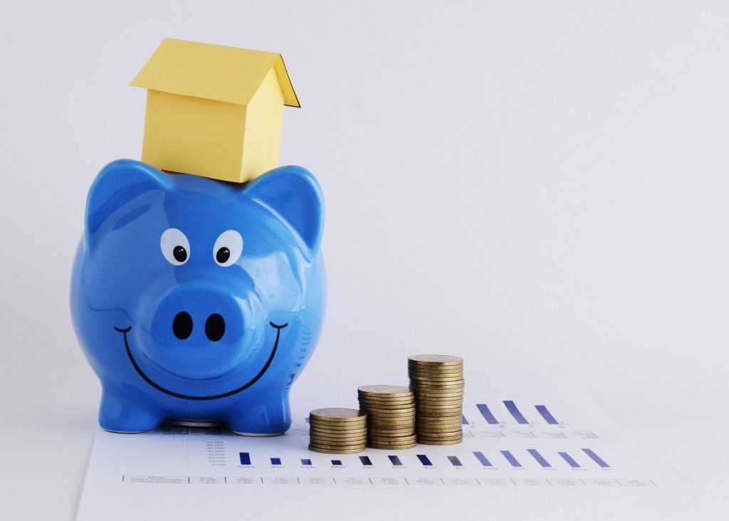 Piggy bank and paper house and coins stack for mortgage loans concept
