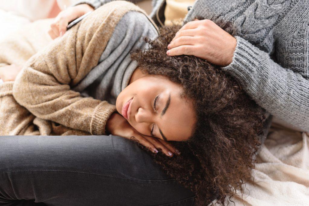 girlfriend laying head on boyfriend's lap