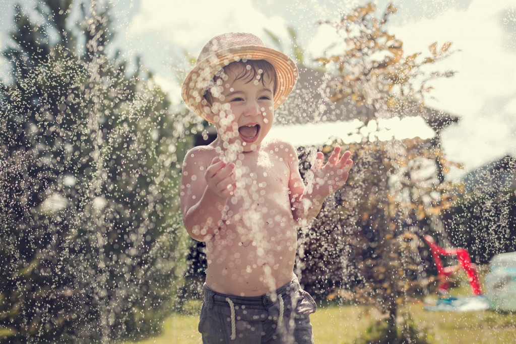 child playing in the sprinklers