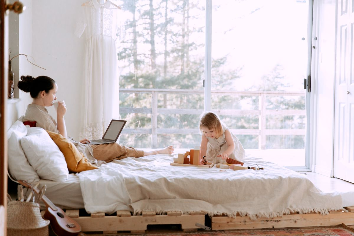 woman working on bed with daughter