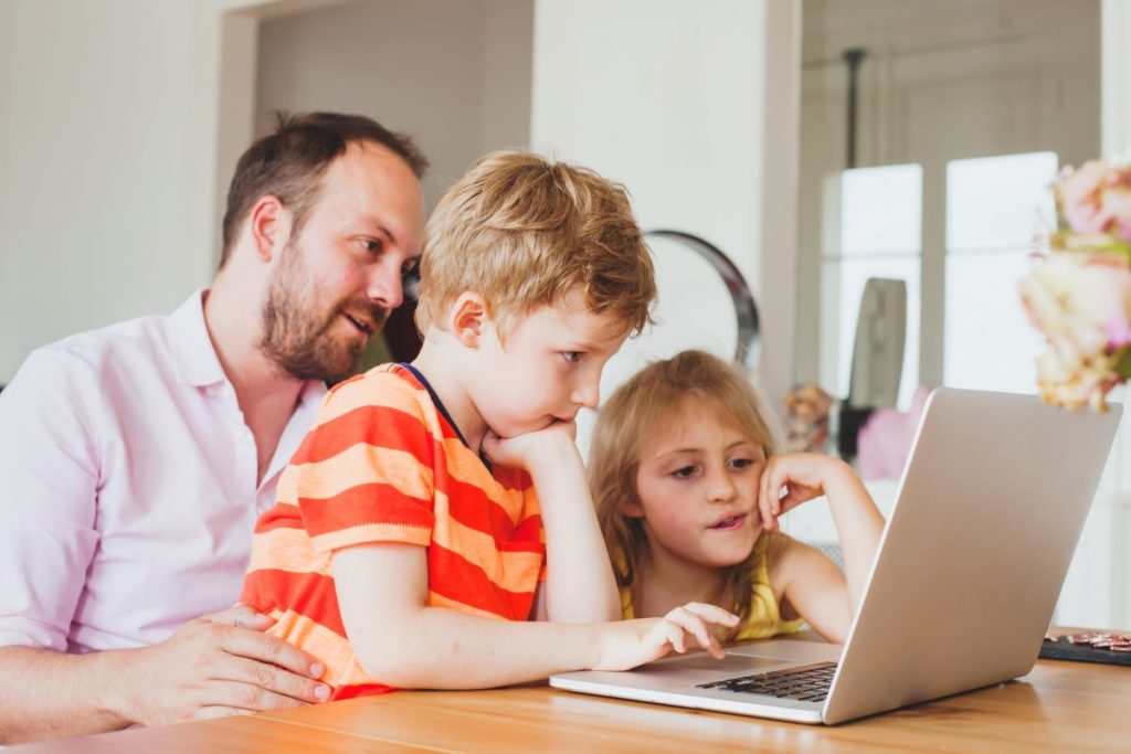 father teaching his kids on his laptop