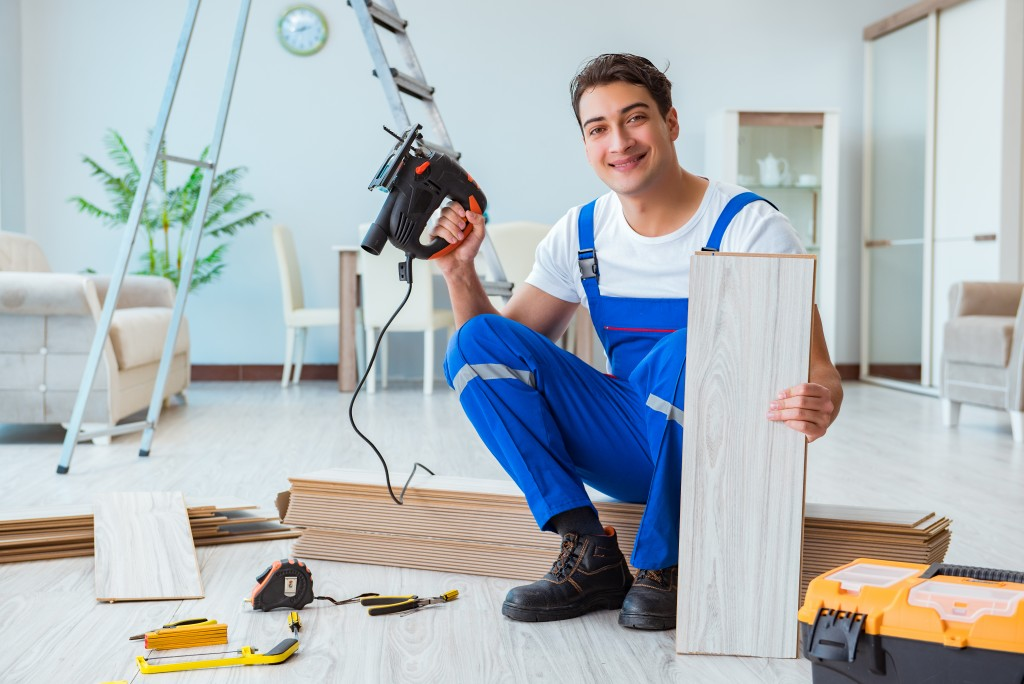 handyman with a drill and plank