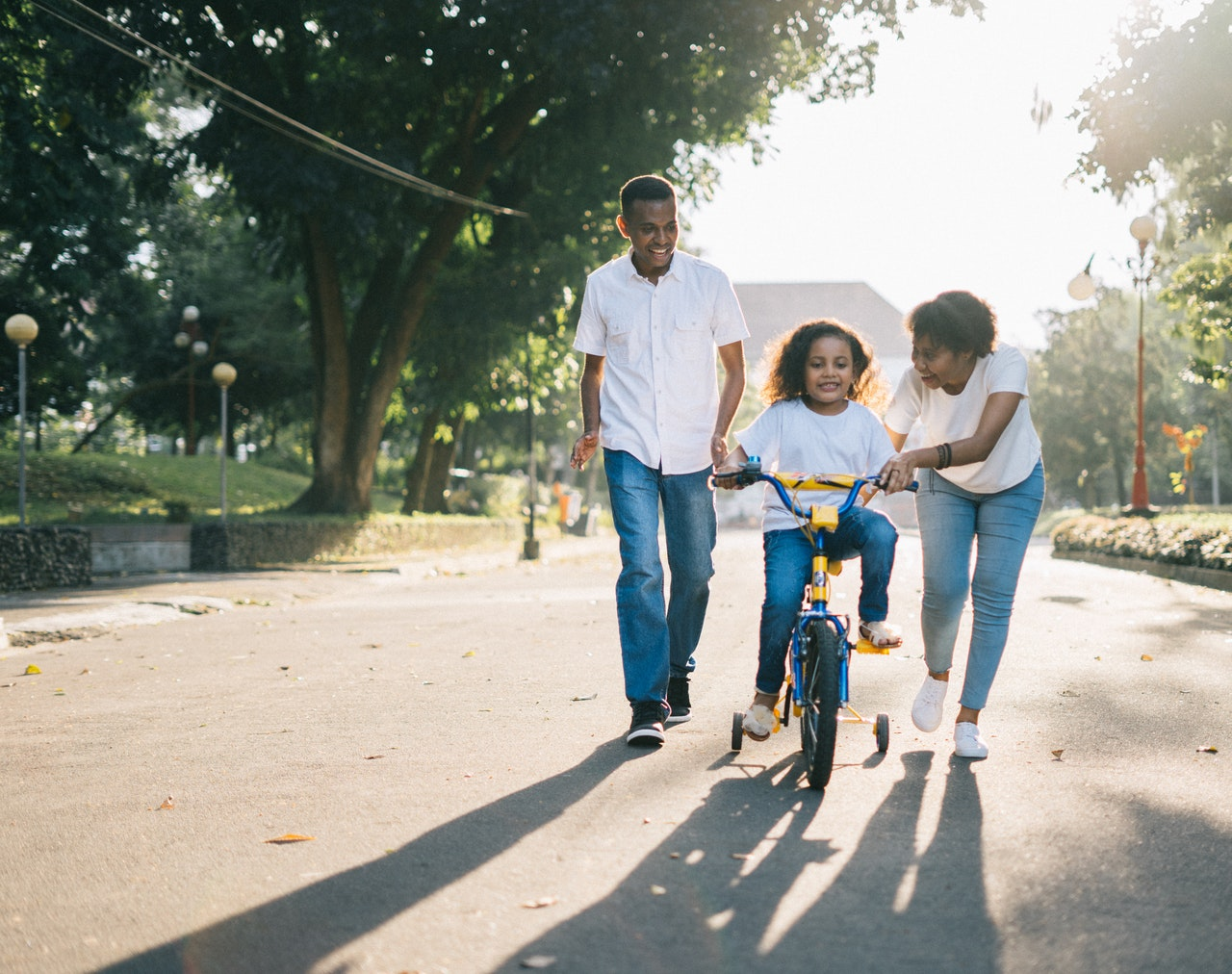 family teaching daughter to ride a bike