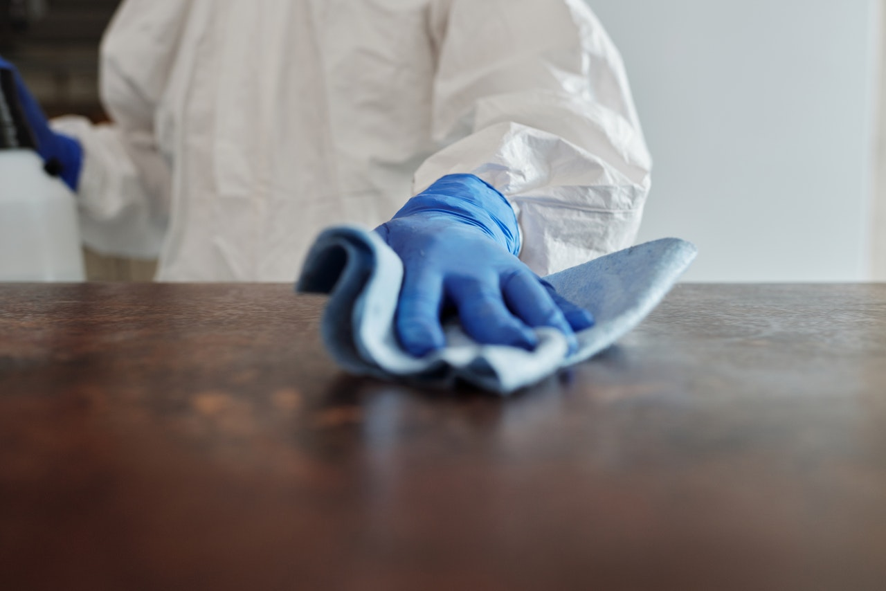 person disinfecting a surface