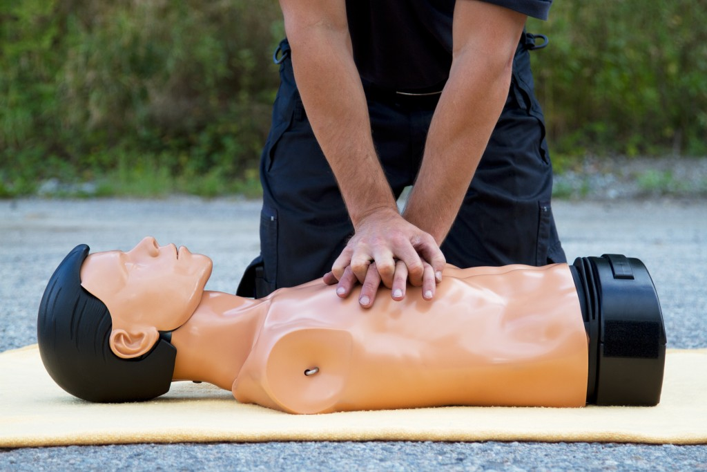person performing CPR on a doll