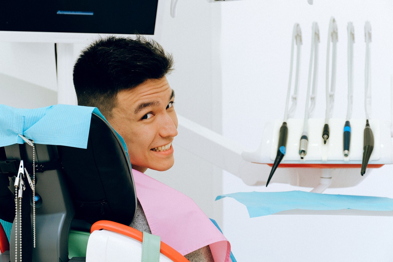 man sitting at the dentist's chair smiling looking back
